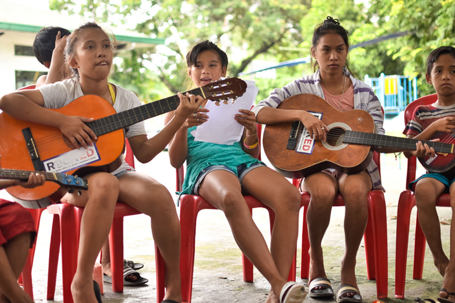 Street children singing and playing guitar - street education photos