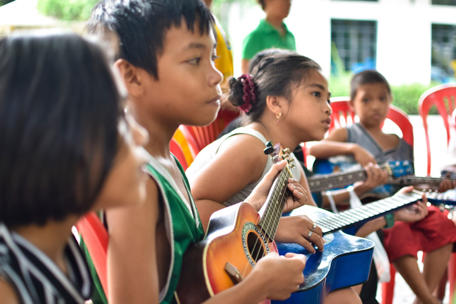 Street children learning to play ukulele and guitars