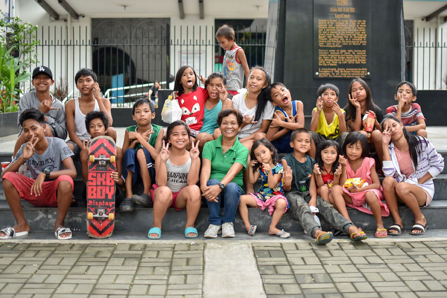 Smiling street children with volunteer teacher sitting on a pavement - street children photos