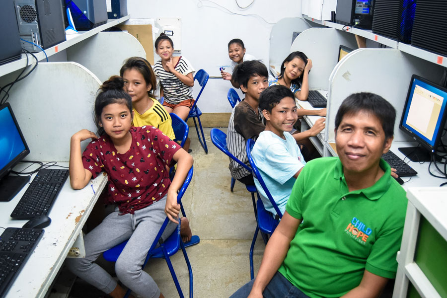 Smiling street children in front of computer cubicles with their volunteer teacher - street education photos