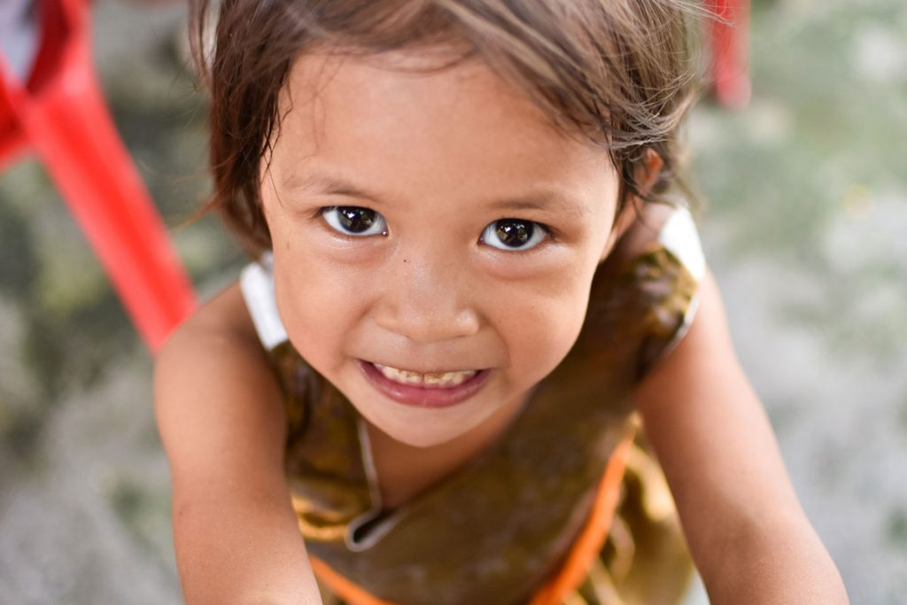 Happy child looking at a staff from Childhope, an NGO for children in the Philippines