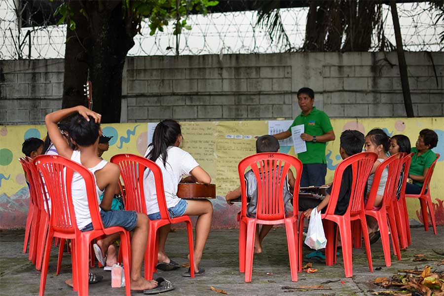 Kids and volunteer in a skills development session as a solution on how to help the street children