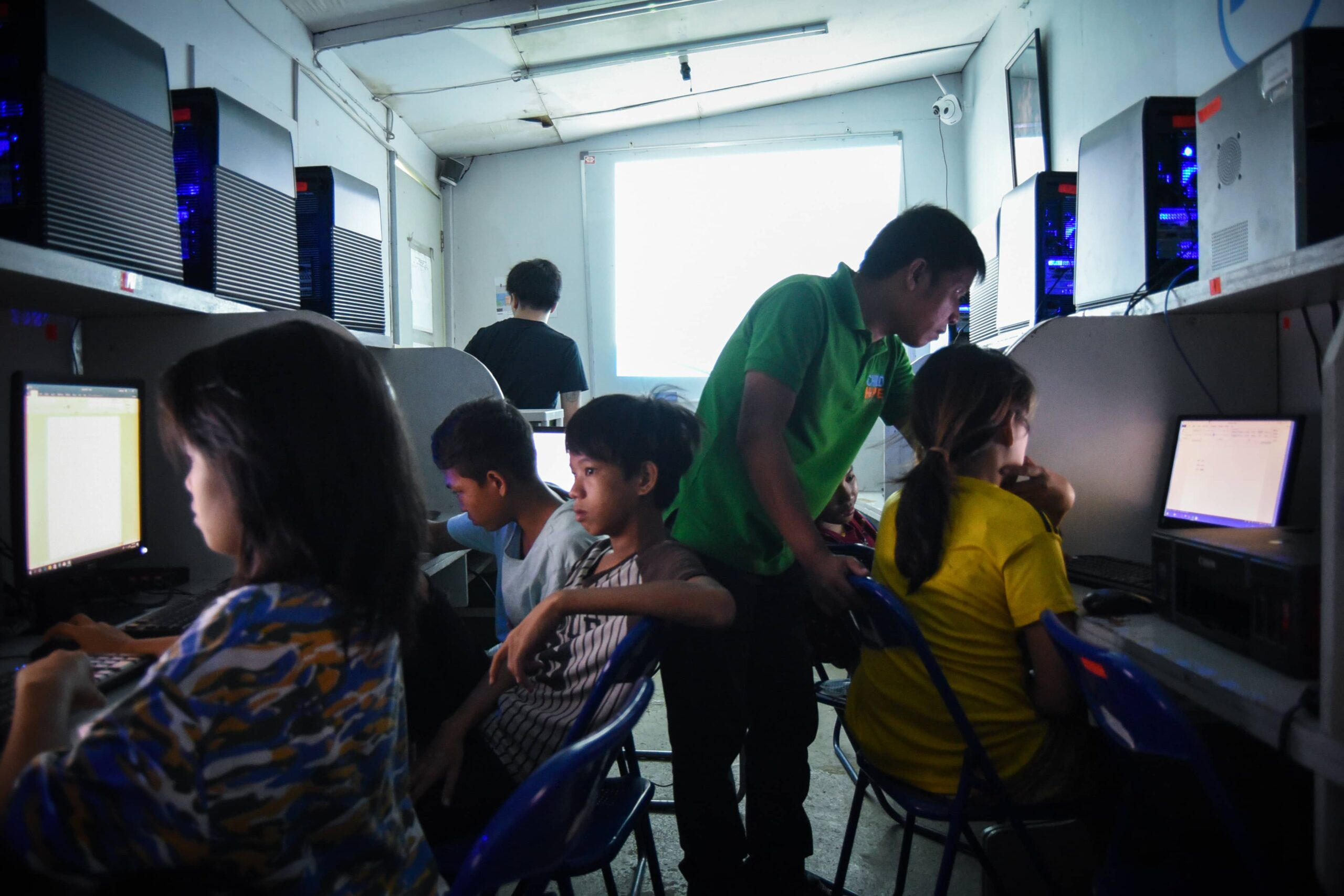 Street educator teaching street children how to use a computer